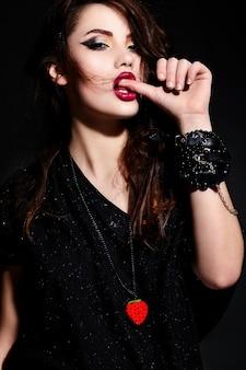Jonge donkerbruine vrouw in zwarte kleding, die haar duim bijt