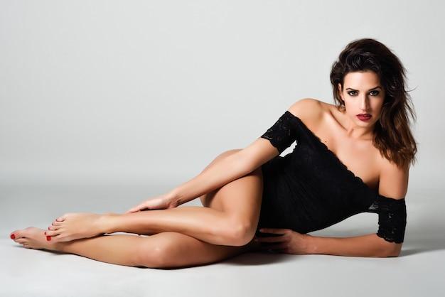 Jonge donkerbruine vrouw in zwarte lingerie die op de vloer ligt.
