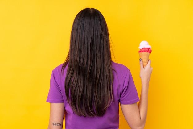Jonge donkerbruine vrouw met een cornetroomijs in achterpositie