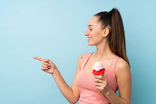 Jonge donkerbruine vrouw met een cornetroomijs over geïsoleerde blauwe muur die aan de kant richten om een product te presenteren