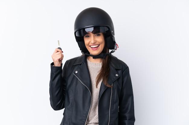 Jonge donkerbruine vrouw met een motorhelm en een sleutel over geïsoleerde witte muur houden