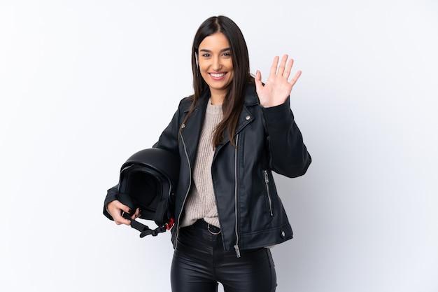 Jonge donkerbruine vrouw met een motorhelm over het geïsoleerde witte muur groeten met hand met gelukkige uitdrukking