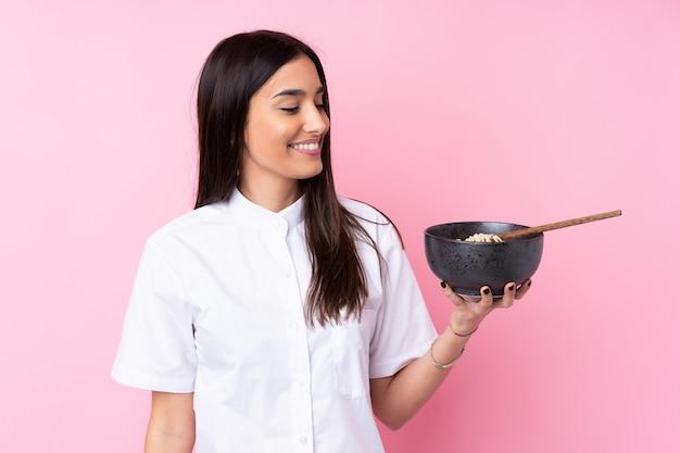 Jonge donkerbruine vrouw met gelukkige uitdrukking terwijl het houden van een kom van noedels met eetstokjes