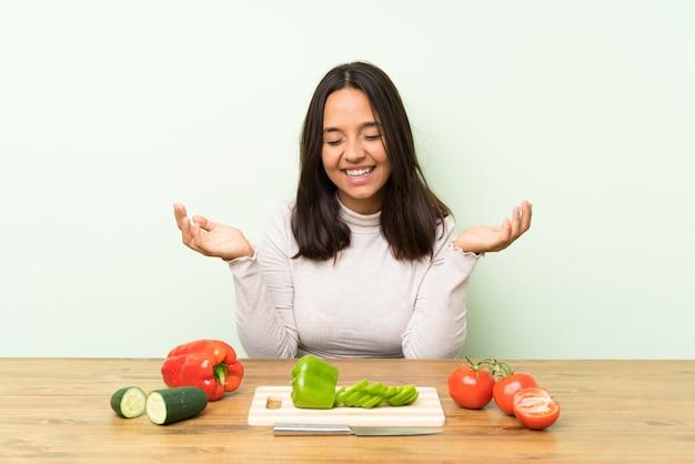 Jonge donkerbruine vrouw met groenten het lachen
