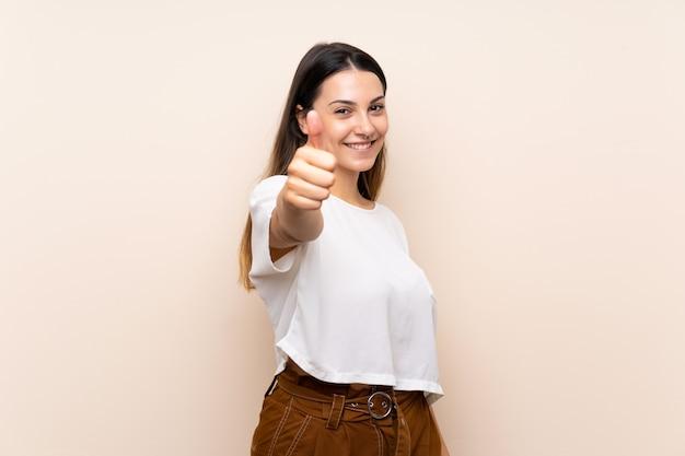 Jonge donkerbruine vrouw met omhoog duimen omdat er iets goeds is gebeurd