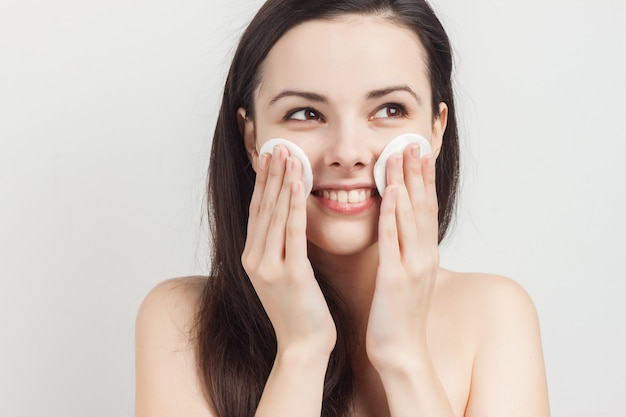Jonge donkerbruine vrouw met sponsen om de huid in haar handen te reinigen