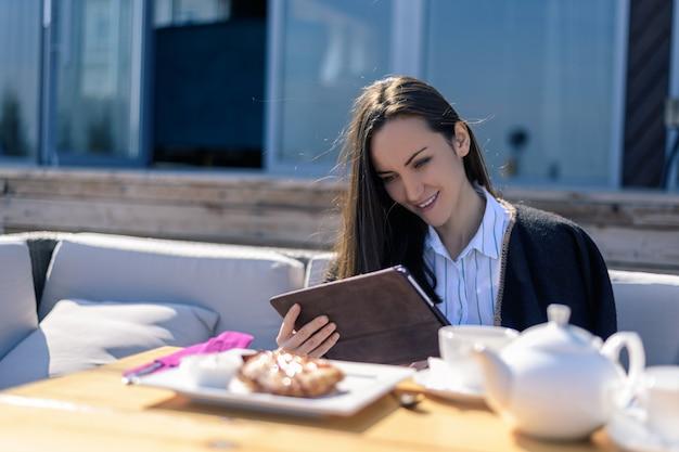 Jonge donkerbruine vrouw op het terras in een de zomerkoffie die ontbijt met een tablet in haar handen heeft