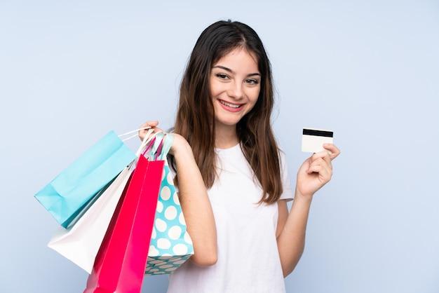 Jonge donkerbruine vrouw over blauwe muur met boodschappentassen en een creditcard