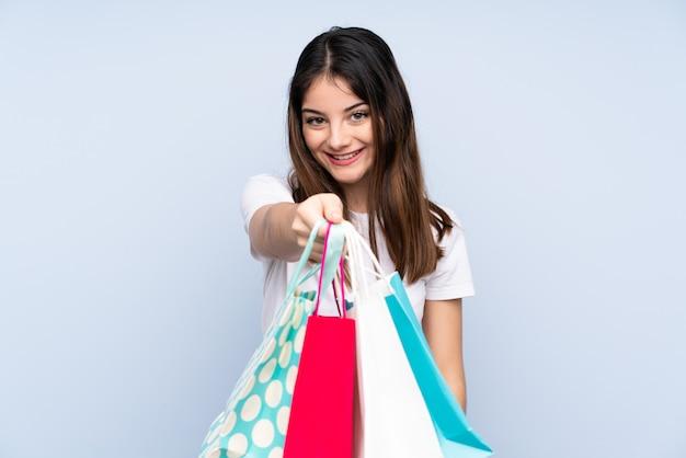 Jonge donkerbruine vrouw over blauwe muurholding het winkelen zakken en het geven van hen aan iemand