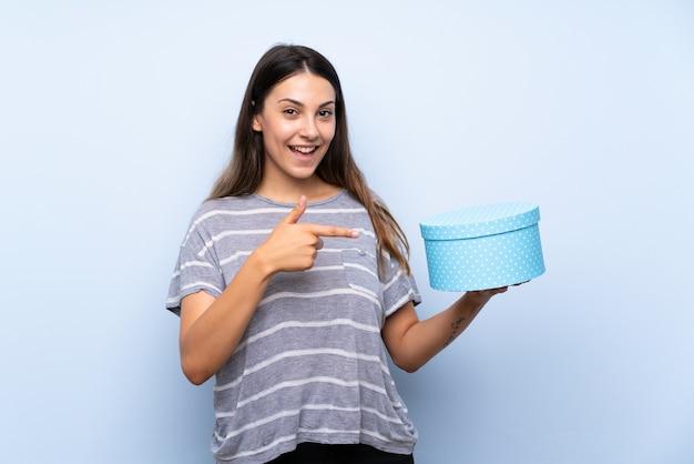 Jonge donkerbruine vrouw over de geïsoleerde blauwe doos van de achtergrondholdingsgift