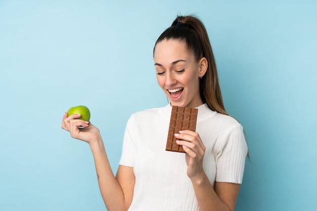 Jonge donkerbruine vrouw over geïsoleerde blauwe muur die een chocoladetablet in één hand en een appel in de andere nemen