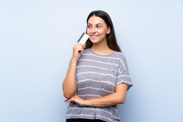 Jonge donkerbruine vrouw over geïsoleerde blauwe muur die een creditcard houdt