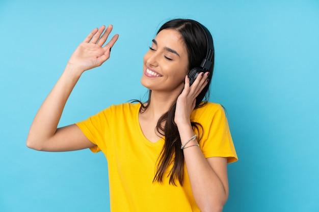 Jonge donkerbruine vrouw over geïsoleerde blauwe muur het luisteren muziek en het dansen