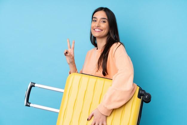 Jonge donkerbruine vrouw over geïsoleerde blauwe muur in vakantie met reiskoffer en het maken van overwinningsgebaar