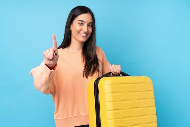 Jonge donkerbruine vrouw over geïsoleerde blauwe muur in vakantie met reiskoffer en het tellen