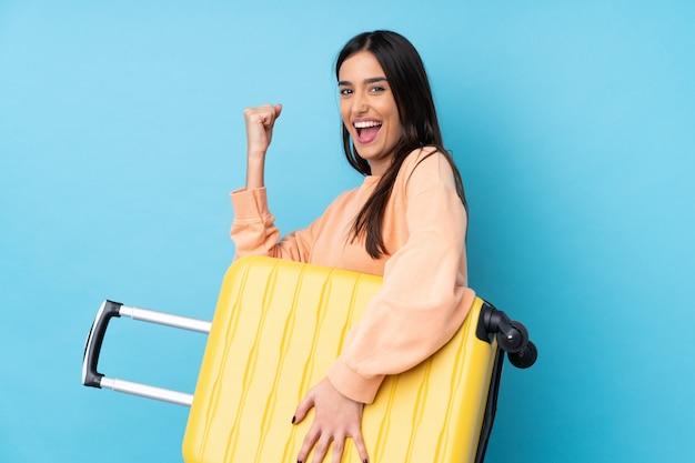 Jonge donkerbruine vrouw over geïsoleerde blauwe muur in vakantie met reiskoffer