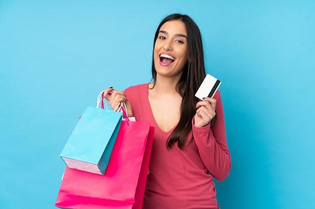 Jonge donkerbruine vrouw over geïsoleerde blauwe muurholding het winkelen zakken en een creditcard