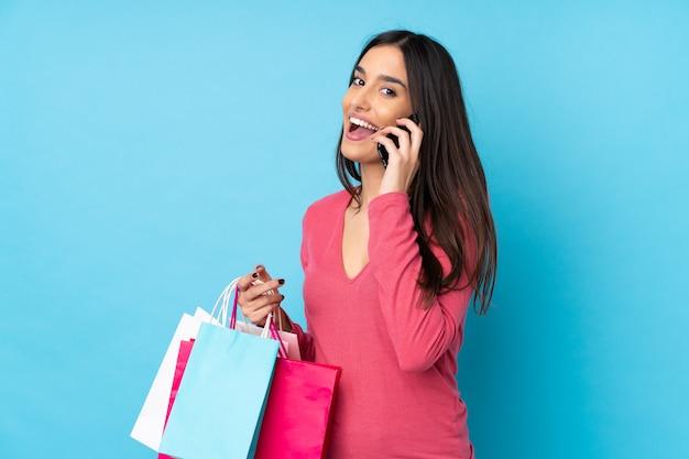 Jonge donkerbruine vrouw over geïsoleerde blauwe muurholding het winkelen zakken en het roepen van een vriend met haar celtelefoon