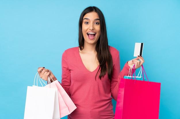 Jonge donkerbruine vrouw over geïsoleerde blauwe muurholding het winkelen zakken en verrast