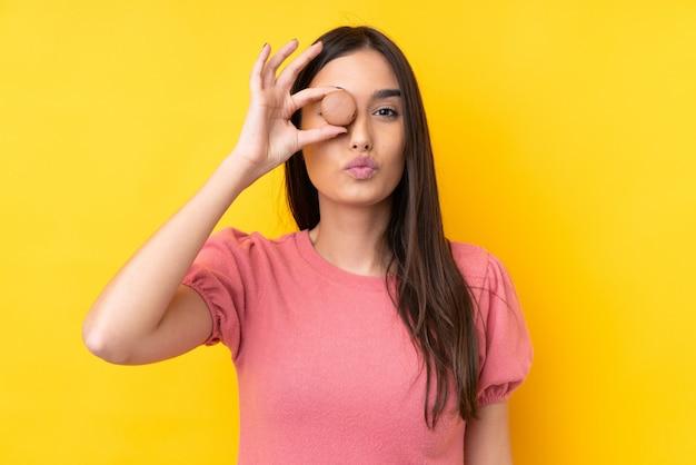 Jonge donkerbruine vrouw over geïsoleerde gele muur die kleurrijke franse macarons met grappig gezicht houden