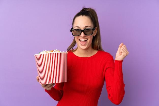 Jonge donkerbruine vrouw over geïsoleerde purpere muur met 3d glazen en holding een grote emmer popcorns
