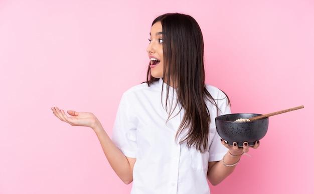 Jonge donkerbruine vrouw over geïsoleerde roze muur met verrassingsgelaatsuitdrukking terwijl het houden van een kom van noedels met eetstokjes