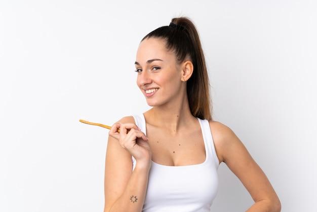 Jonge donkerbruine vrouw over geïsoleerde witte muur met een tandenborstel en een gelukkige uitdrukking