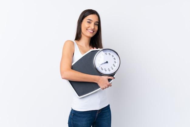 Jonge donkerbruine vrouw over geïsoleerde witte muur met weegmachine