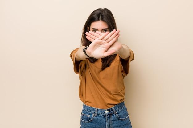 Jonge donkerbruine vrouw tegen een beige die een ontkenningsgebaar doet