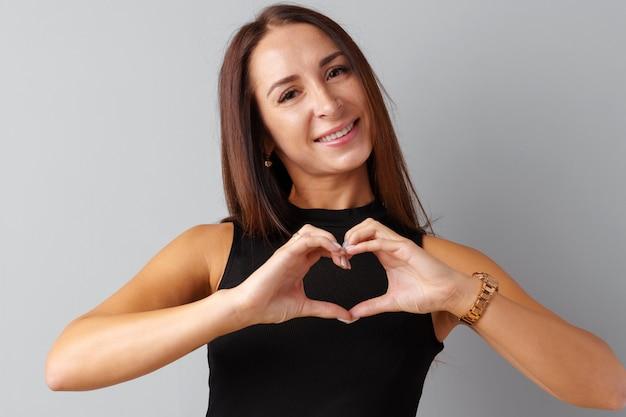 Jonge donkerbruine vrouw wat betreft haar hart met haar handen