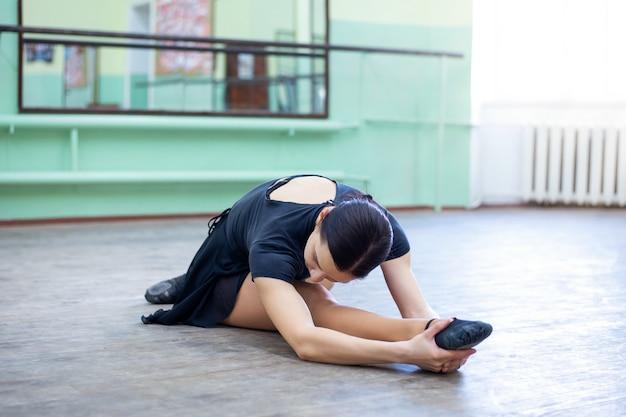 Jonge donkerbruine vrouwelijke danser die oefeningen in balletstudio maakt