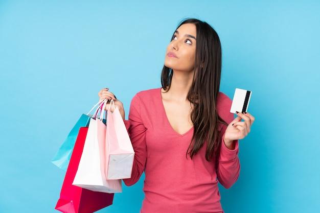 Jonge donkerbruine vrouwenholding het winkelen zakken en een creditcard en het denken