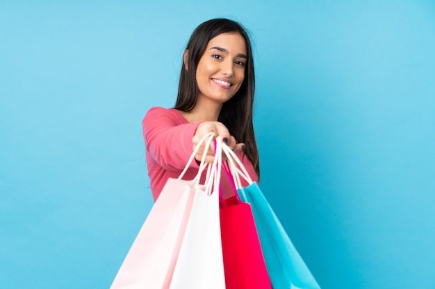 Jonge donkerbruine vrouwenholding het winkelen zakken en het geven van hen aan iemand