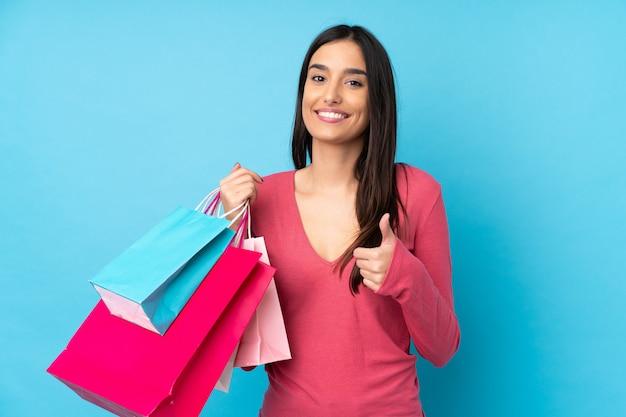 Jonge donkerbruine vrouwenholding het winkelen zakken en met omhoog duim