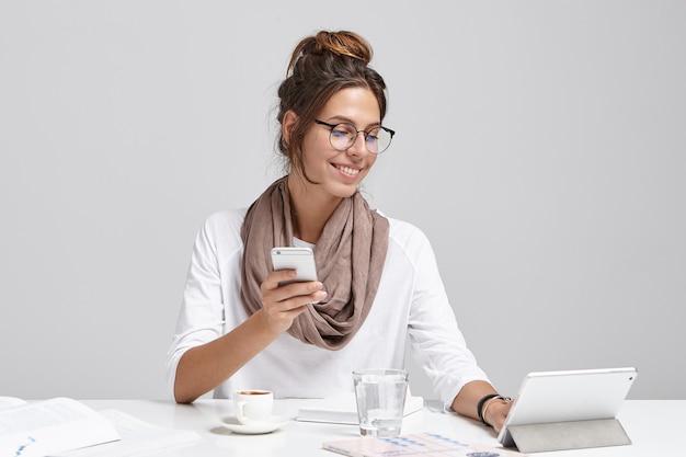 Jonge donkerbruine vrouwenzitting bij bureau