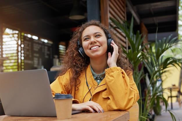 Jonge donkere gekrulde student vrouw zitten op een terras van een café, luistert naar muziek en droomt van een weekendfeest, gekleed in een gele jas, koffie drinken, werkt op een laptop.
