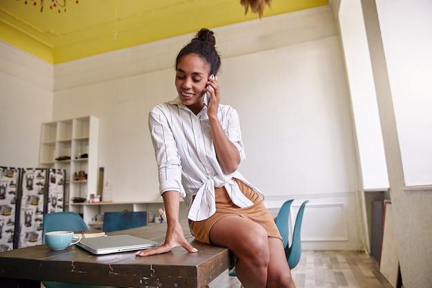 Jonge donkere huid mooie vrouw in gestreept wit overhemd met broodje kapsel met leuk gesprek aan de telefoon, zittend op tafel en kijken op haar hand