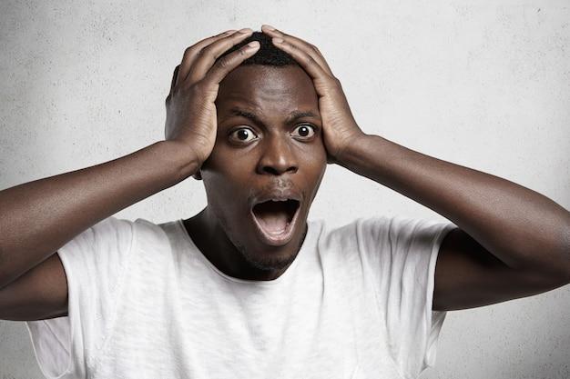 Jonge donkere klant of werknemer die zijn hand op zijn hoofd houdt, geschokt door ongekende verkoopprijzen.