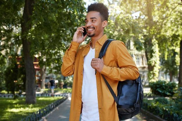 Jonge donkere lachende man draagt een wit overhemd en een wit t-shirt met een rugzak op één schouder, loopt in het park en praat aan de telefoon met zijn vriend, lacht en geniet van de dag.