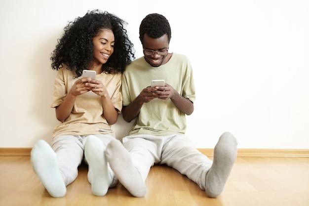 Jonge donkere man en vrouw in vrijetijdskleding tijd samen binnenshuis doorbrengen, online videogames spelen op elektronische apparaten