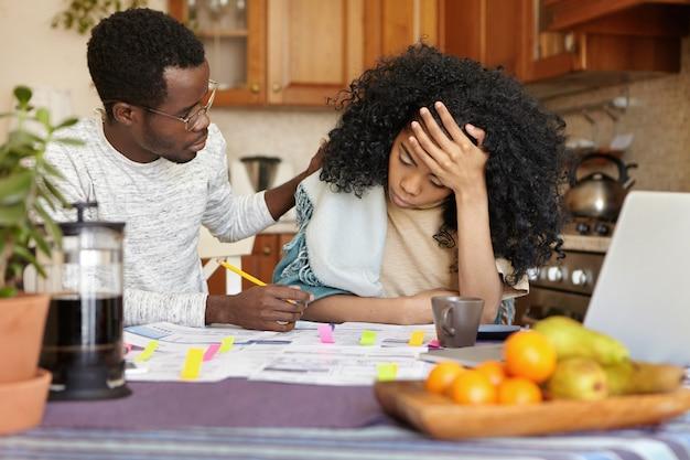 Jonge, donkere vrouw die zich gestrest voelt, het hoofd vasthoudt in wanhoop