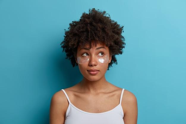 Jonge, donkere vrouw met afro-haar brengt hydrogel-zilvervlekken onder de ogen aan, vermindert wallen, verwijdert donkere kringen. huid zorg concept