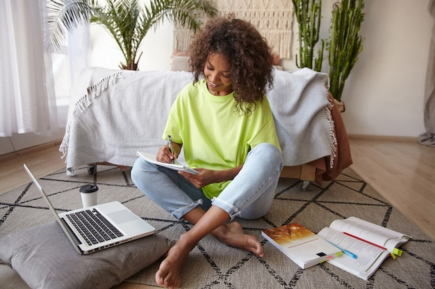 Jonge donkere vrouw met bruin krullend haar studeert in de slaapkamer, maakt aantekeningen met een blij gezicht, draagt een spijkerbroek en een geel t-shirt Gratis Foto