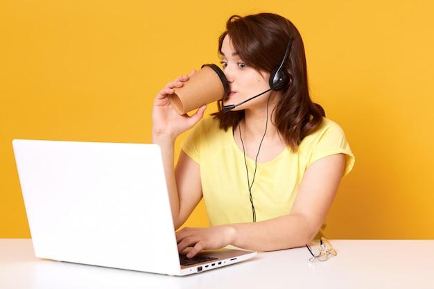 Jonge donkerharige dame, werkzaam in het callcenter, geeft advies aan de klant via een videogesprek, vrouw met hoofdtelefoon en microfoon