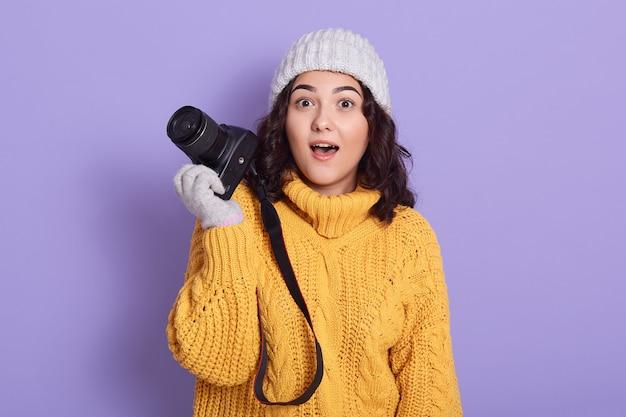 Jonge donkerharige fotograaf die geschokt is over de foto die ze heeft gemaakt