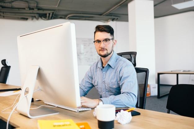 Jonge donkerharige man in glasess en een blauw shirt werkt met een computer op zijn bureaublad in kantoor. hij lacht naar de camera.