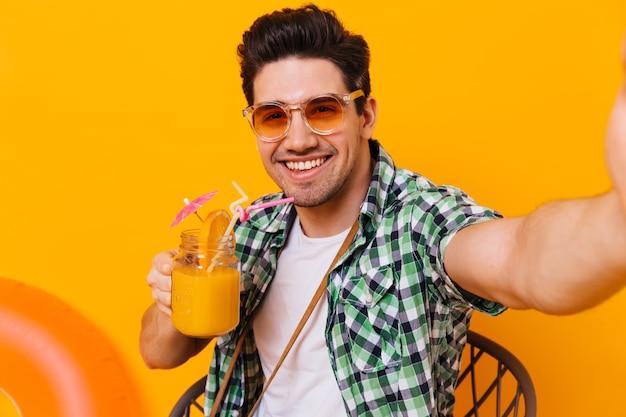 Jonge donkerharige man in groen shirt en oranje bril geniet van cocktail en neemt selfie op geïsoleerde ruimte.