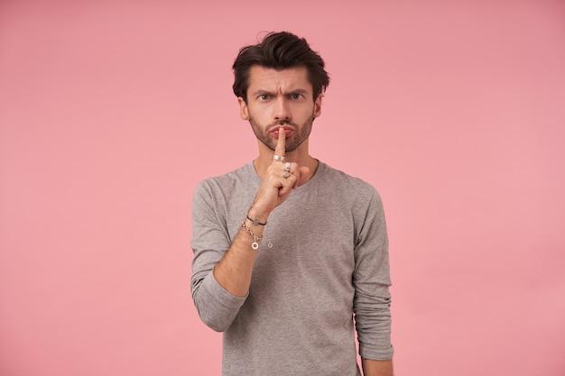 Jonge donkerharige man met baard die met wijsvinger op zijn mond kijkt, vraagt om stilte te bewaren met ernstig gezicht, staande in vrijetijdskleding