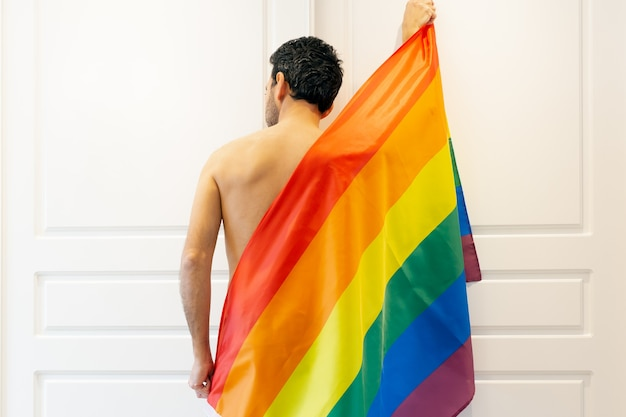 Jonge donkerharige man van achteren met blote rug bedekt met lgbtqi + regenboogvlag in het midden van de afbeelding met witte gesloten deuren