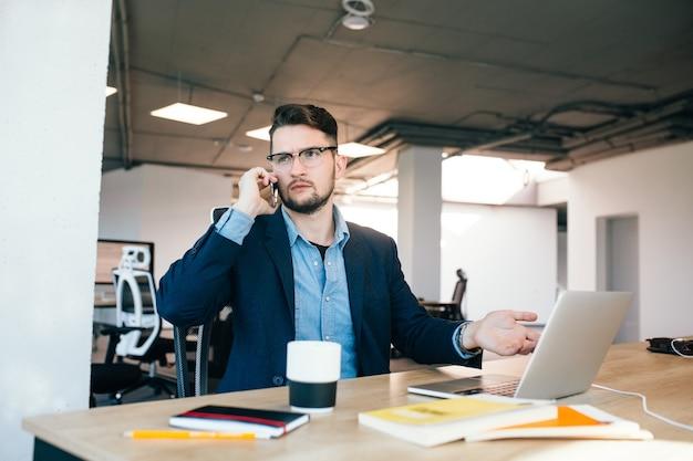 Jonge donkerharige man werkt aan de tafel in kantoor. hij draagt een blauw shirt met een zwarte jas. hij is aan het bellen en kijkt van streek.